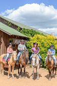 foto of wooden horse  - cowboy family of four on horses on background of wooden building - JPG