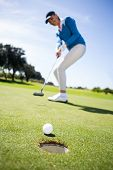 stock photo of ball cap  - Female golfer putting her ball on a sunny day at the golf course - JPG
