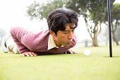picture of cheater  - Golfer trying to flick ball into hole at the golf course - JPG