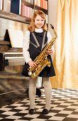 image of saxophones  - Girl in school uniform dress holding alto saxophone standing near the piano indoors - JPG