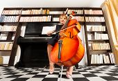 foto of cello  - One small girl in school uniform dress playing on the cello sitting near the piano and shelves with books - JPG