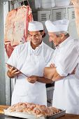 stock photo of slaughterhouse  - Happy multiethnic male butchers looking at tablet computer in butchery - JPG