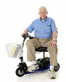 picture of crippled  - A senior man happily looking at the viewer from his electric scooter - JPG