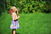 stock photo of blowers  - little girl play with bubble blower on green lawn - JPG
