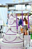 foto of unity candle  - Wedding cake with flowers and violet candles - JPG