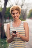 picture of jogger  - Cheerful female jogger choosing music on her smartphone - JPG