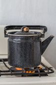 picture of kettles  - Old kettle on a gas stove flame burn not boiling - JPG