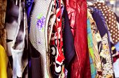 stock photo of flea  - some different used clothes hanging on a rack in a flea market - JPG