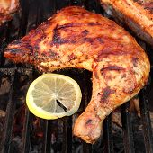 stock photo of bbq party  - BBQ Roasted Chicken Leg Quarter On The Hot Charcoal Grill Close - JPG