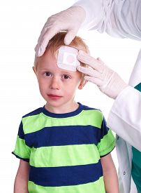 stock photo of forehead  - Child gets injury on the forehead and the nurse helps with getting plaster on the wound so it can heal - JPG