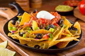 stock photo of jalapeno  - A plate of delicious tortilla nachos with melted cheese sauce ground beef jalapeno peppers red onion green onions tomato black olives salsa and sour cream with guacamole dip - JPG