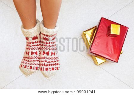 Cute Photo Of Woman's Feet With Christmas Socks, Top View Point And Christmas Gifts.
