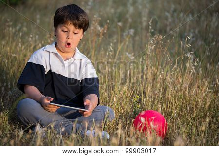 little scared boy surfing in the internet with digital tablet