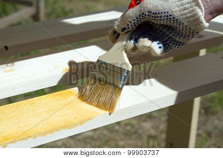 Female hand paints brown a wooden furniture outdoors closeup