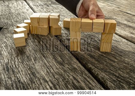 Close Up Of Businessman Forming A Bridge Of Small Wooden Blocks