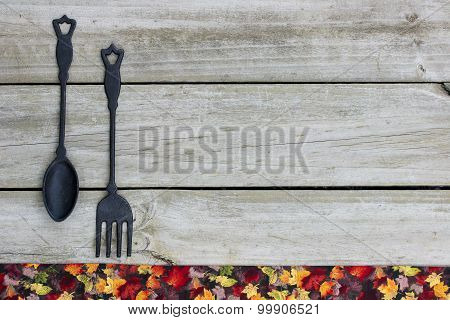 Blank sign with cast iron spoon and fork by autumn leaves border