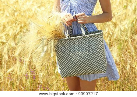 Woman holding bag with sheaf outdoors