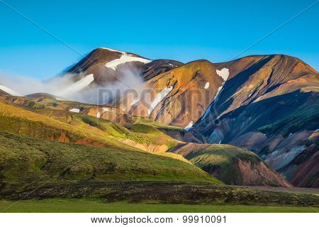 Early summer morning in the National Park Landmannalaugar, Iceland. In the hollows of rhyolitic mountain snow