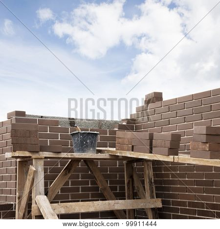 House under construction. Bucket with masonry cement and brown clinker bricks at scaffolding boards. Space for text.