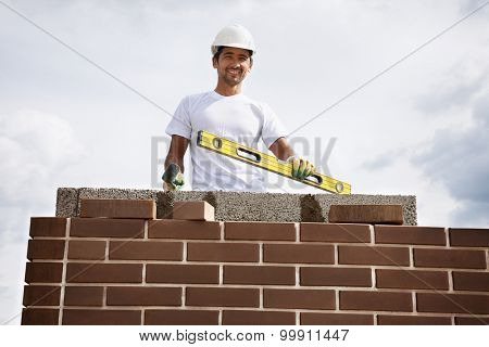 Portrait of construction bricklayer worker against sky.