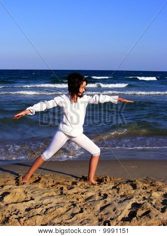 Young girl doing yoga on the beach