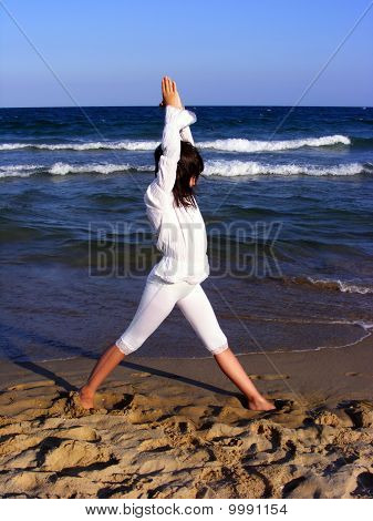 Young girl doing yoga on the beach - triangle asana
