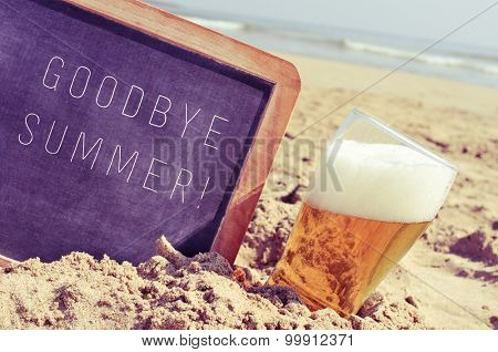closeup of a chalkboard with the text goodbye summer written in it and a glass of beer, on the sand of a beach