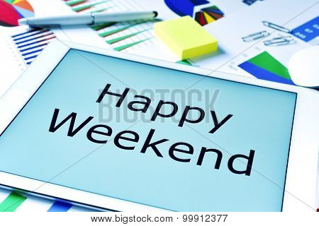 the text happy weekend in the screen of a tablet, placed on a table full of charts