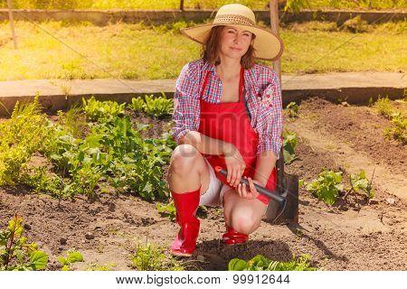 Woman With Gardening Tool Working In Garden