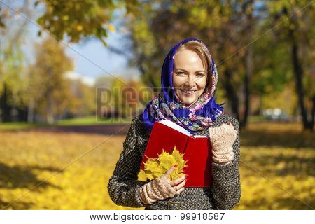Portrait close up of young beautiful woman and red book, on background autumn park