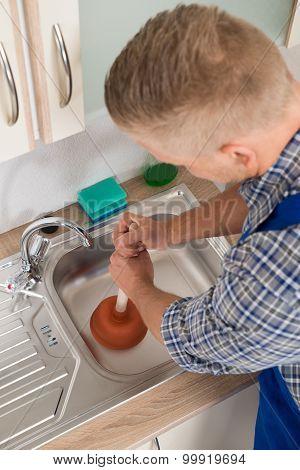 Worker Pressing Plunger In Sink