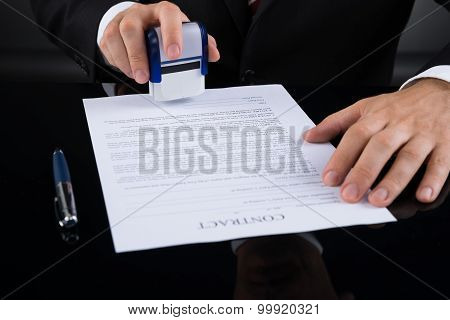 Businessperson With Stamper And Contract Paper