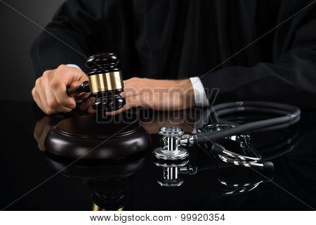 Close-up Of Judge Hitting Gavel With Stethoscope