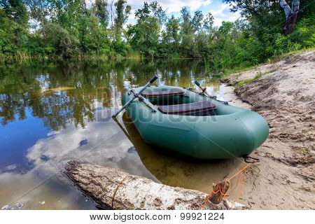 inflatable boat on lake shore in summer forest