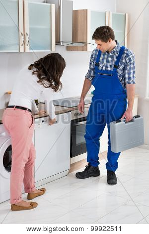 Woman Showing Dishwasher To Worker