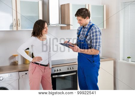 Woman And Repairman In Kitchen