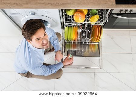 Man Putting Dishwasher Soap Tablet In Dishwasher