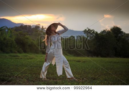 Blonde Girl In Vietnamese Dress Looks Into Distance On Field