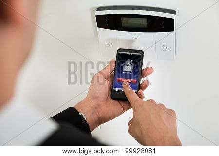 Businessperson Disarming Security System With Mobile Phone