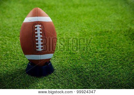 American football standing on holder on american football field