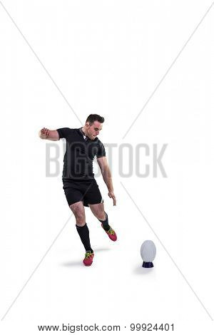 Rugby player kicking the ball on white background