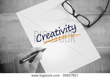 The word creativity against left hand writing on white page on working desk