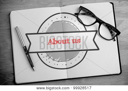 The word about us and banner drawing against overhead of open notebook with pen and glasses