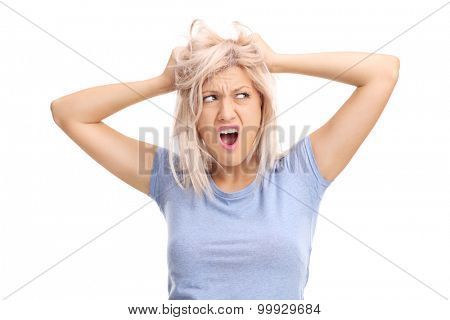 Frustrated young woman pulling her hair and screaming isolated on white background