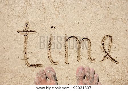 Concept or conceptual time text handwritten in sand for natural, symbol, tourism or conceptual designs with feet