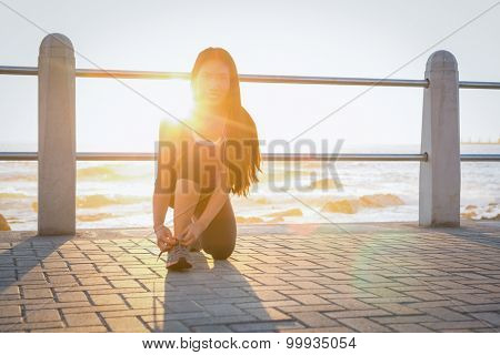 Portrait of smiling fit woman tying her shoelace at promenade on a sunny day