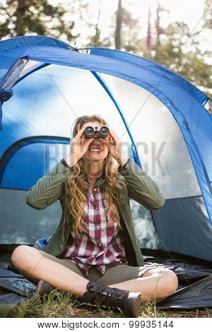 Smiling blonde camper looking through binoculars while sitting in tent