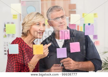 Puzzled business team looking post its on the wall in the office
