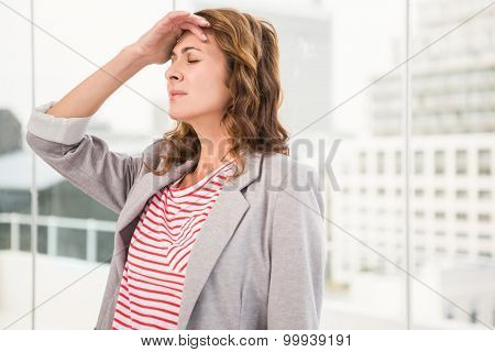 Overworked casual businesswoman having a headache in the office