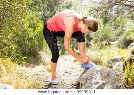 Blonde athlete tying her shoelace in the nature